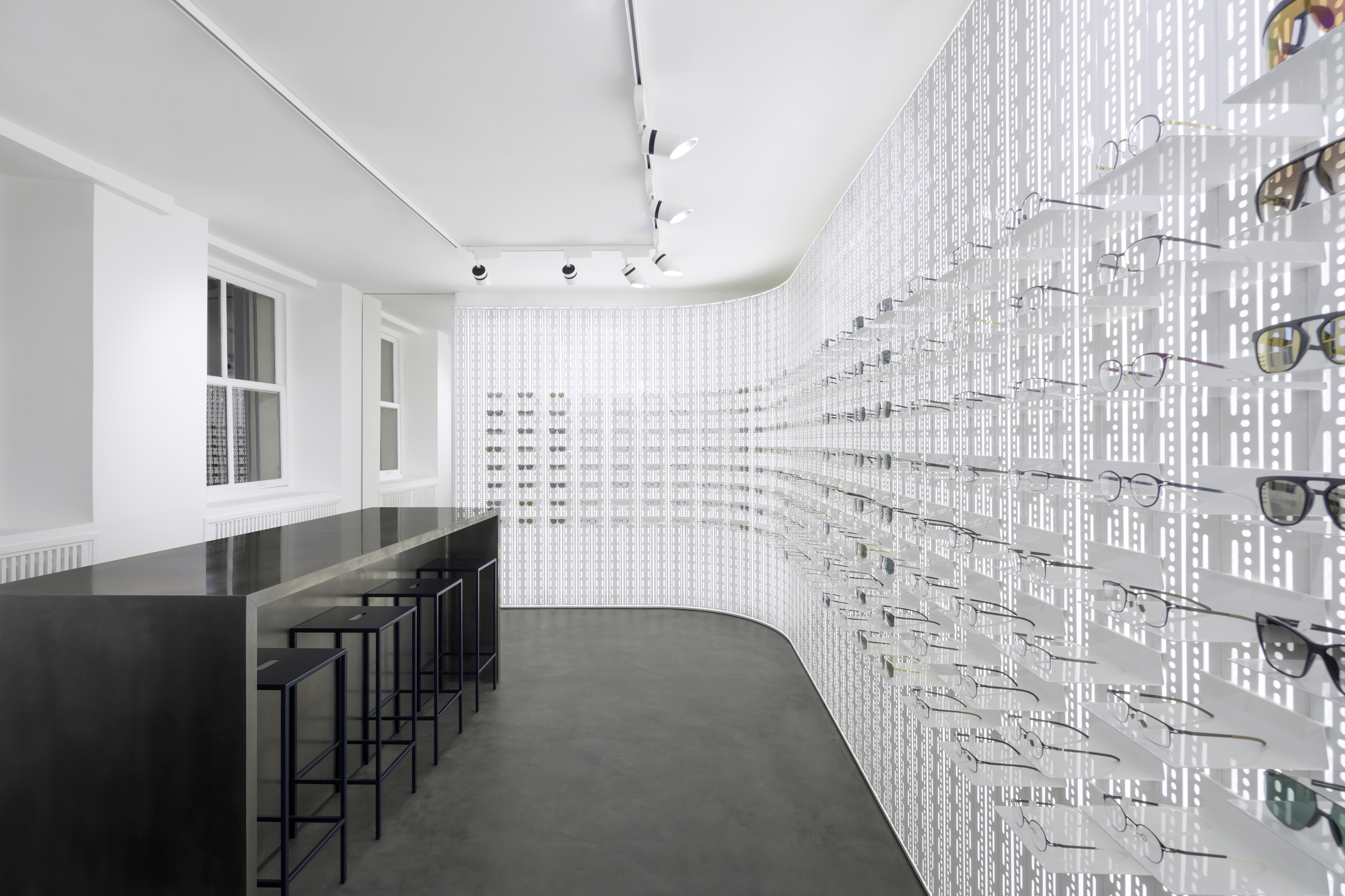 The interior of the MYKITA Shop Paris with the expansive MYKITA WALL and custom-made furniture.